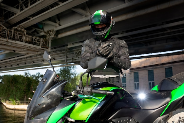 Motociclista parada sob a ponte sobre a estrada esperando a chuva parar