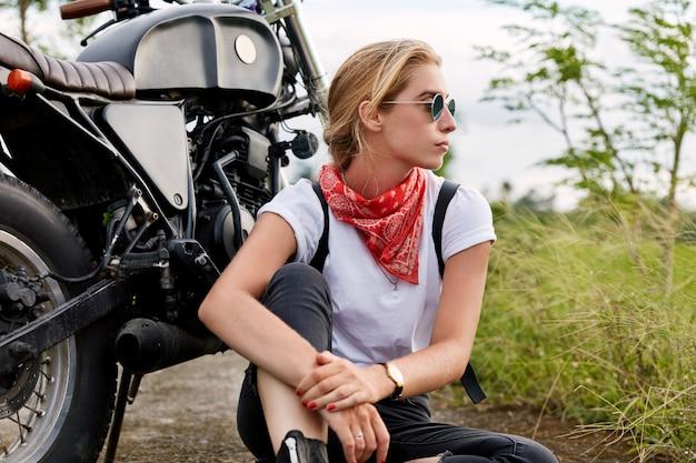 Motociclista pensativa, imersa em pensamentos, usa roupas da moda, desvia o olhar com expressão pensativa, senta-se no chão perto de uma motocicleta, cobre um longo destino. pessoas, transporte e liberdade