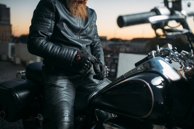 Motociclista posa em uma motocicleta na cidade no pôr do sol, helicóptero clássico. bicicleta vintage, estilo de vida livre, ciclismo