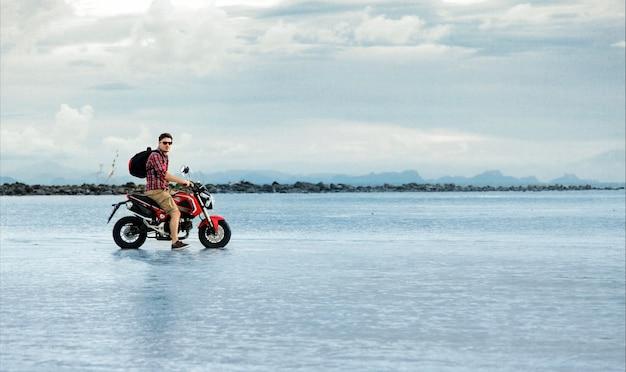 Motociclista posando com sua motocicleta na água do mar