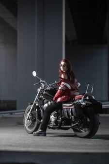 Motociclista posando sexualmente em uma motocicleta à noite na cidade
