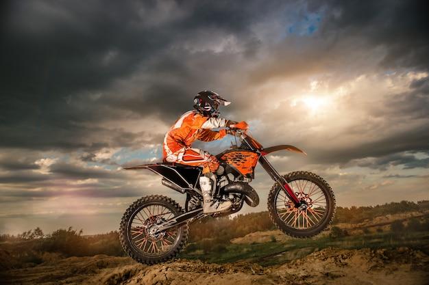 Motociclista profissional dirigindo nas montanhas e mais abaixo na pista off-road. é pôr do sol.