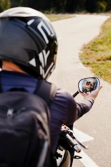 Motociclista que fixa o espelho retrovisor de moto