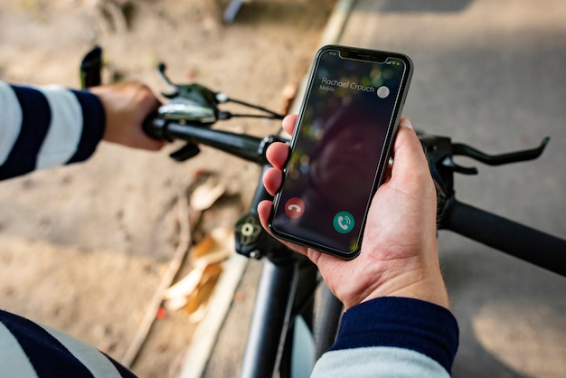Motociclista, segurando, smartphone, com, entrante, chamada