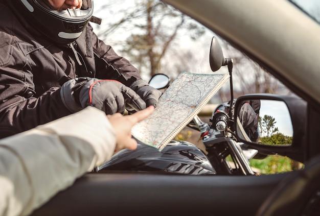 Motociclista sênior pedindo ao motorista do carro a direção no mapa rodoviário