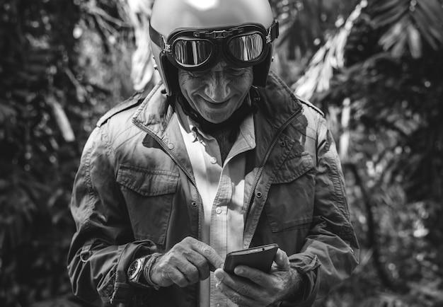 Motociclista sênior usando um telefone celular