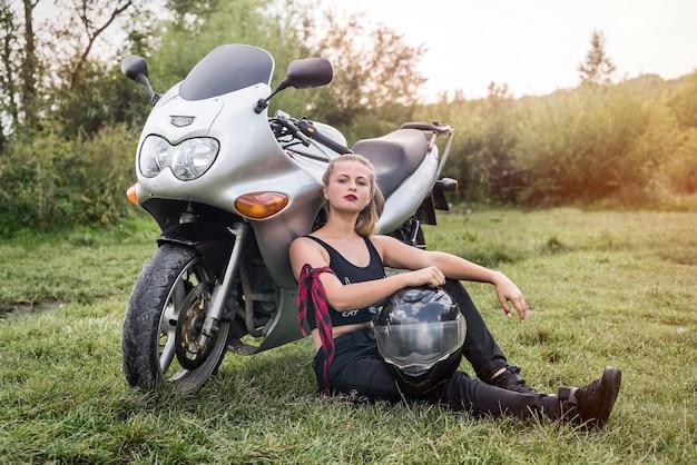 Motociclista sentada perto de uma motocicleta com um capacete nos braços