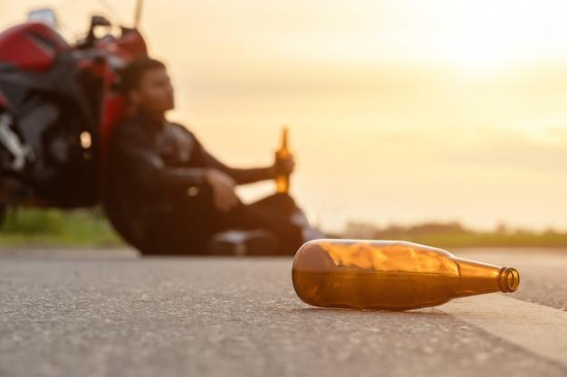 Motociclista sentado na estrada ao lado de sua moto, beber um álcool ou cerveja