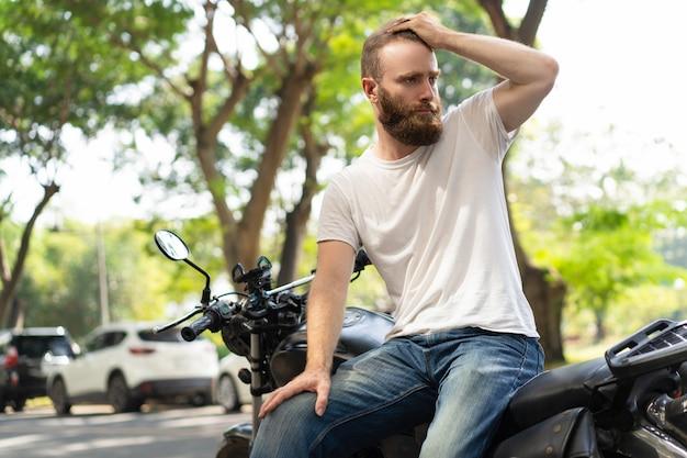 Motociclista sério, apoiando-se na moto quebrada