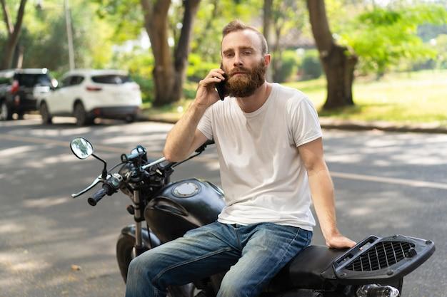 Motociclista sério chamando assistência na estrada