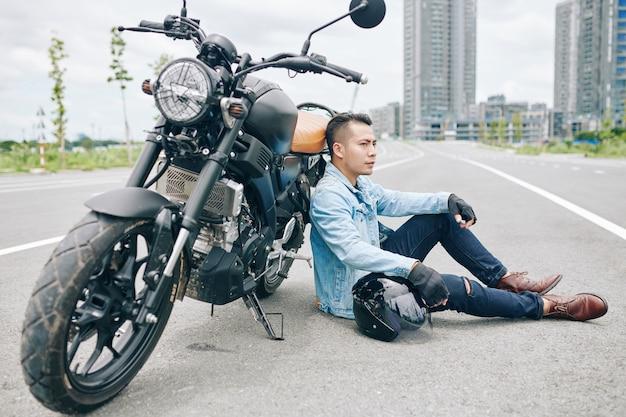 Motociclista vietnamita sério cansado sentado na estrada vazia ao lado de sua motocicleta quebrada e olhando para longe