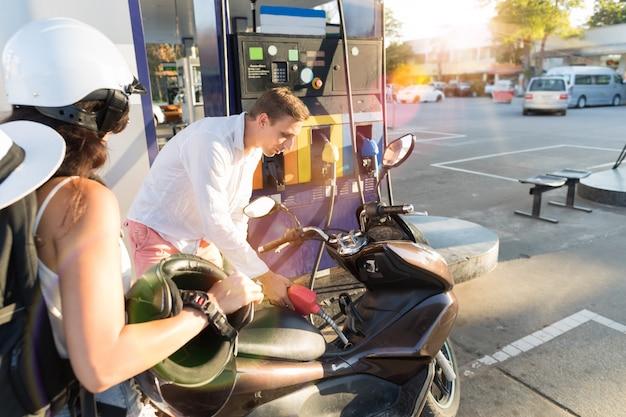 Motociclistas de homem e mulher motocicleta na estação casal pertol bike