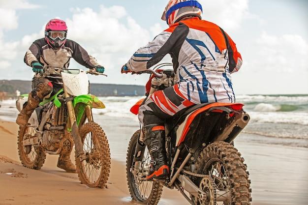 Motociclistas em um traje de proteção sentado em motos em frente ao mar