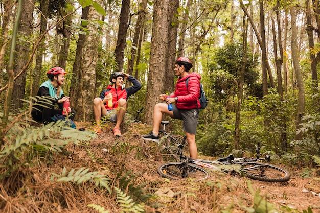 Motociclistas na selva. os motociclistas bebem água. os desportistas estão sentados e apreciando a paisagem.