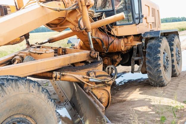 Motoniveladora - equipamento pesado para construção de estradas e terraplenagem. nivelamento e melhoramento da superfície do solo. construção de estradas e comunicações de transporte.