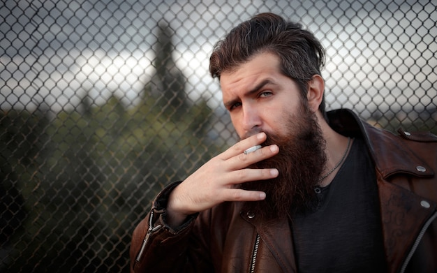 Motoqueiro brutal com uma longa barba, bigode e cabelos grisalhos em uma jaqueta de couro marrom fuma um cigarro