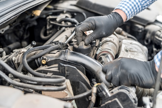 Motor de carro com mãos de trabalhador fecham