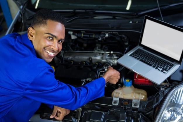 Motor do carro examinando mecânico com ajuda de laptop