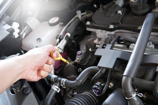 Motor do homem do funcionamento e do reparo do homem do mecânico no centro de serviço do carro.