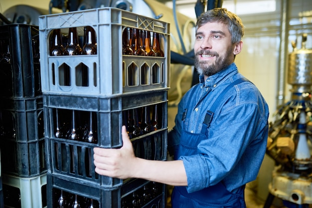 Motor masculino brutal feliz trabalhando no armazém de cerveja