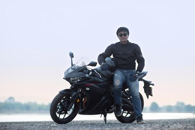 Motorbiker bonito com capacete nas mãos da motocicleta
