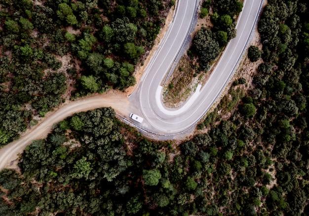 Motorhome estacionado na curva de uma estrada de montanha, vista de cima, de alguns turistas na estrada.