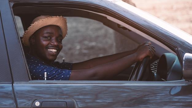 Motorista africano homem sorrindo enquanto está sentado em um carro com a janela da frente aberta.