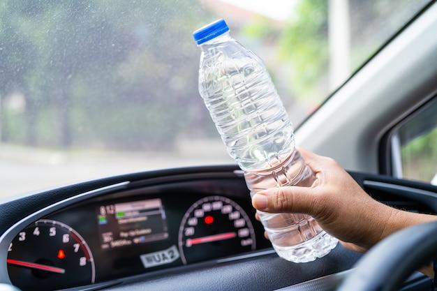 Motorista asiática segurando uma garrafa para beber água enquanto dirige um carro