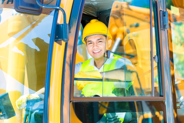 Motorista asiático sentado na cabine do maquinário de construção de um canteiro de obras