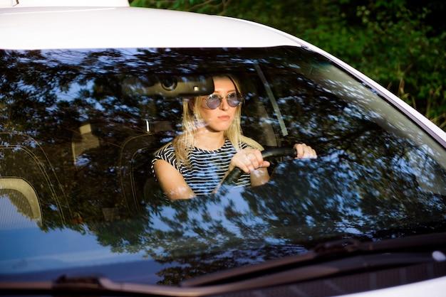 Motorista atraente alegre senta-se no banco do motorista de um carro moderno