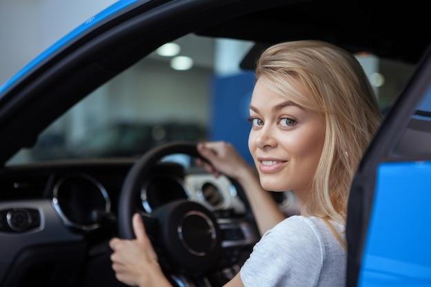 Motorista atraente, sorrindo para a câmera com as mãos no volante de um automóvel novo