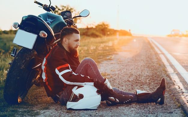 Motorista caucasiano bonito com bela barba deitado em sua motocicleta, colocando a mão esquerda no capacete branco contra o pôr do sol