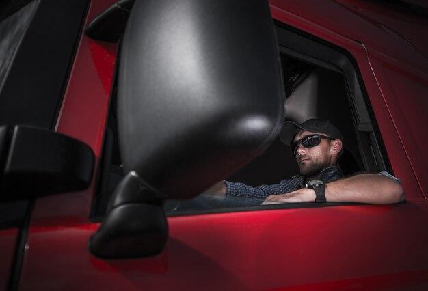 Motorista caucasiano em seu trator vermelho novo brandnew do caminhão.
