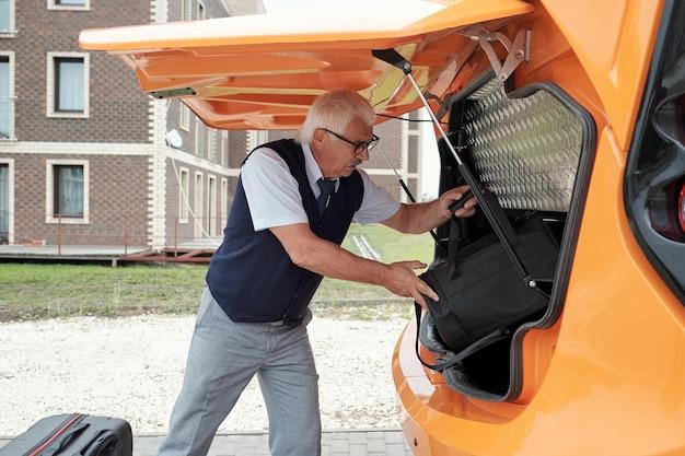 Motorista caucasiano idoso sério de uniforme e óculos, colocando a bagagem no porta-malas aberto antes da viagem