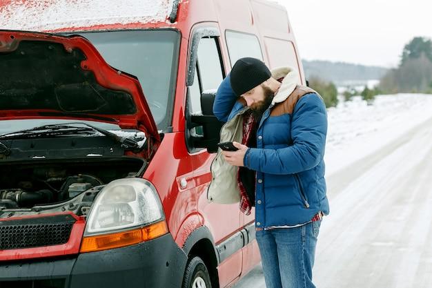 Motorista chamar assistência técnica na estrada no inverno.