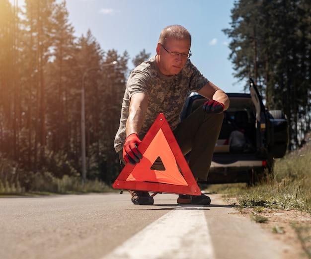 Motorista colocando sinal de alerta com triângulo vermelho na estrada perto de um carro quebrado