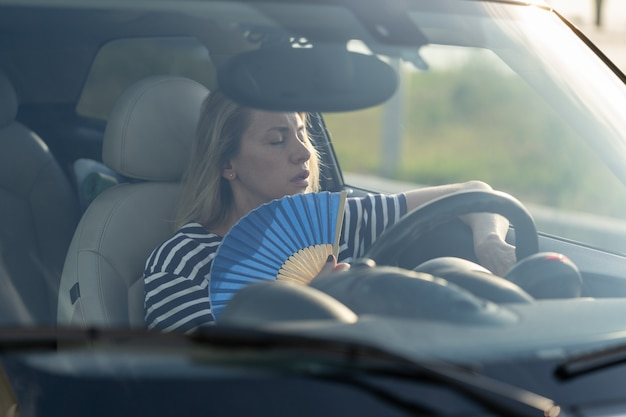 Motorista com ventilador de mão e sofrendo de calor no carro tem problemas com o ar condicionado que não funciona