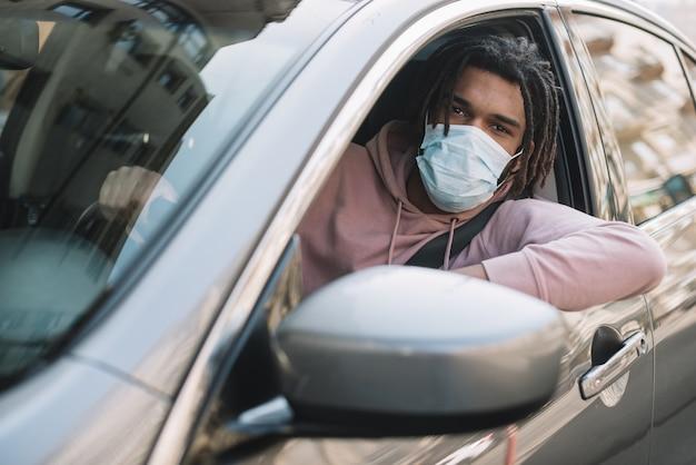 Motorista considerável que desgasta a máscara médica
