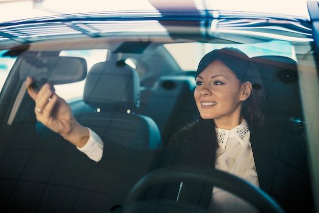 Motorista da jovem mulher que ajusta seu espelho de rearview no carro.