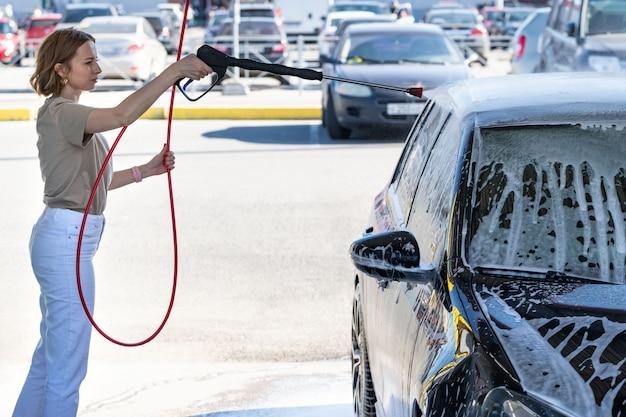 Motorista da jovem mulher que lava na lavagem manual do carro, limpando com espuma, água pressionada. lavagem de carro de autoatendimento