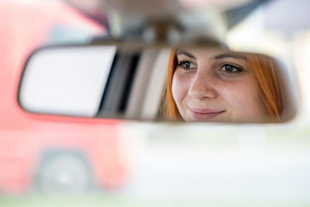 Motorista da jovem mulher que verifica o espelho retrovisor que olha para trás ao dirigir um carro.