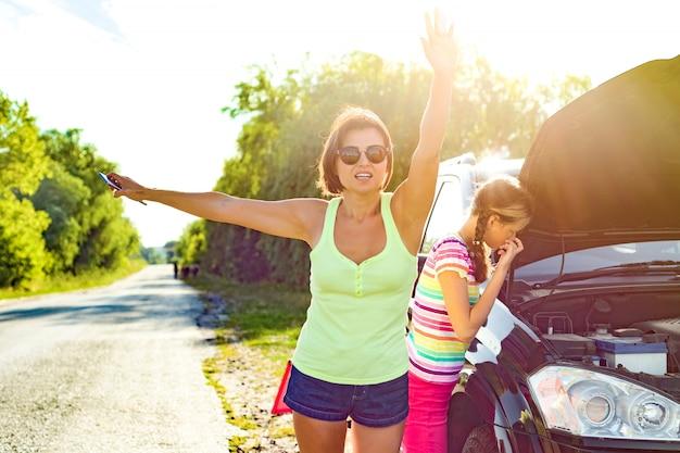 Motorista da mulher com a criança perto de carro quebrado.