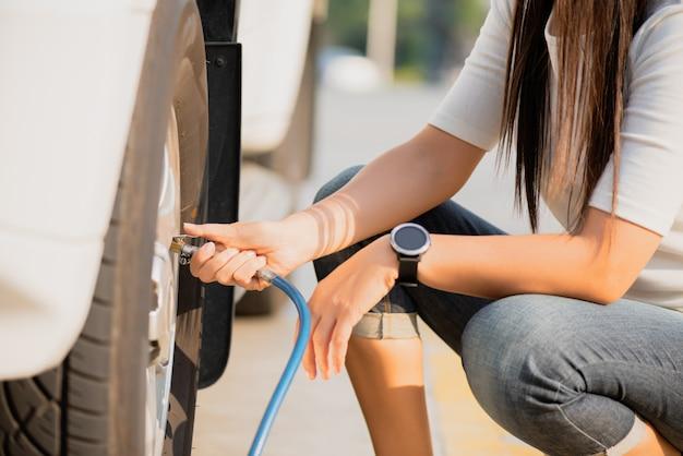 Motorista da mulher que verifica a pressão do ar e que enche o ar nos pneus perto acima.