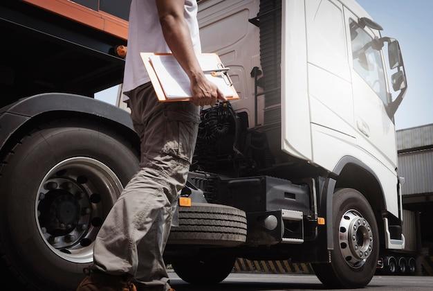 Motorista de caminhão andando segurando a prancheta, verificando a segurança ao redor do caminhão semi