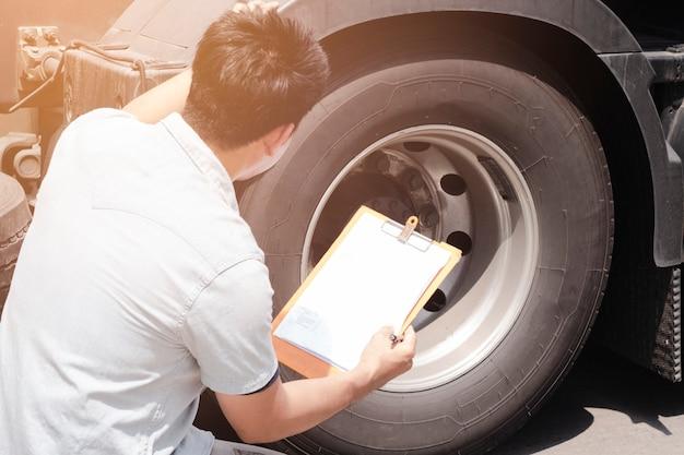 Motorista de caminhão asiático segurando a prancheta, inspecionando a verificação de segurança, um pneu de caminhão