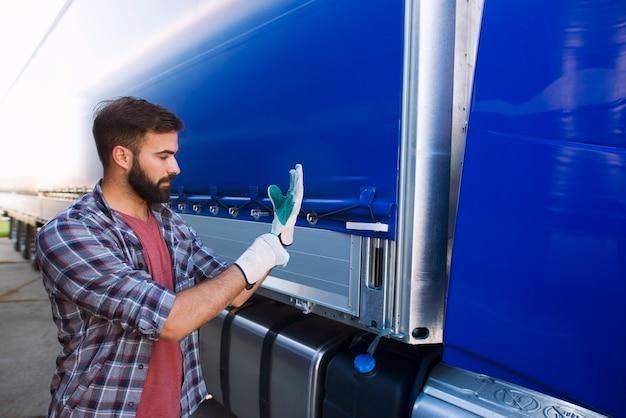 Motorista de caminhão calçando luvas para remover a lona do veículo para descarregar