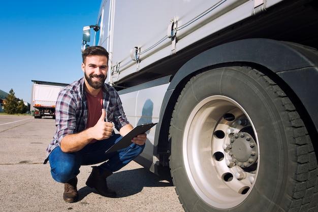 Motorista de caminhão com o polegar para cima inspecionando o estado dos pneus e verificando a pressão