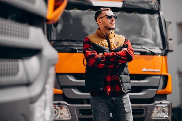 Motorista de caminhão de homem bonito em pé ao lado do caminhão