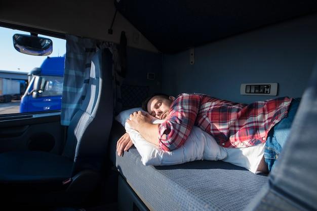 Motorista de caminhão dormindo em sua cabine após trabalhar em longas rotas em horas extras
