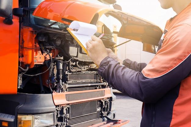 Motorista de caminhão está segurando uma prancheta com inspecionando o motor de um caminhão.